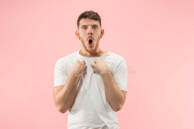 Beautiful male half-length portrait isolated on pink studio backgroud. The young emotional surprised man. Argue, arguing concept. Beautiful male half-length stock photography