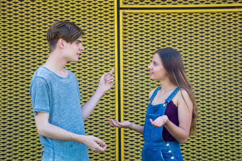 Arguing teenagers gesticulating with question. Arguing older brother with younger sister solving dissagreement and questions of puzzled teenage girl royalty free stock photo