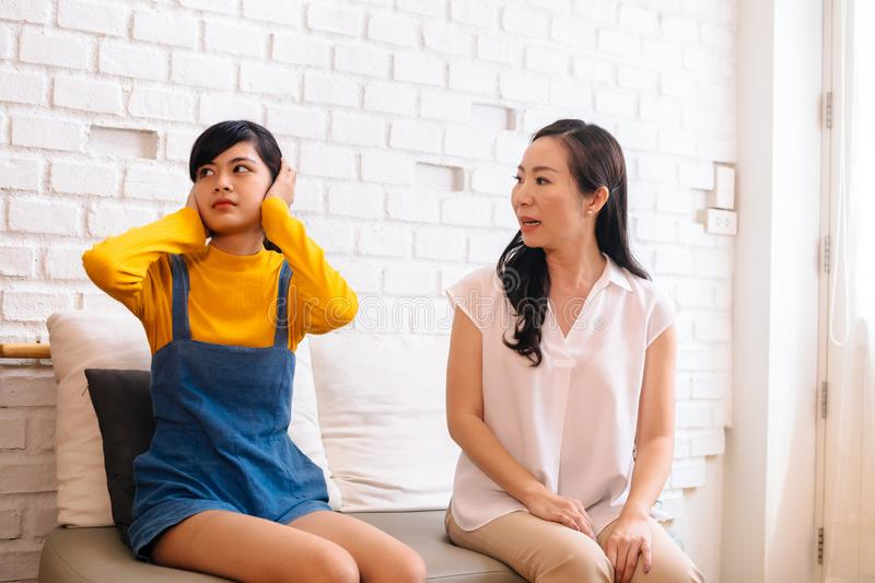 Argument between annoyed Asian teenage daughter and upset middle aged mother. royalty free stock photography