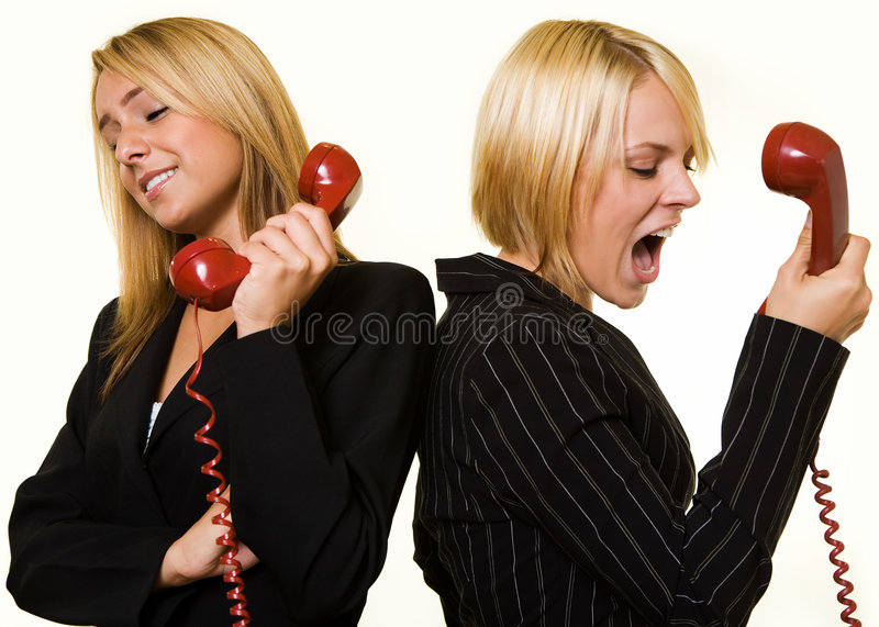 Argument over the phone. Two business women one yelling into the receiver the other holding the phone away from ear to show a loud argument royalty free stock photo