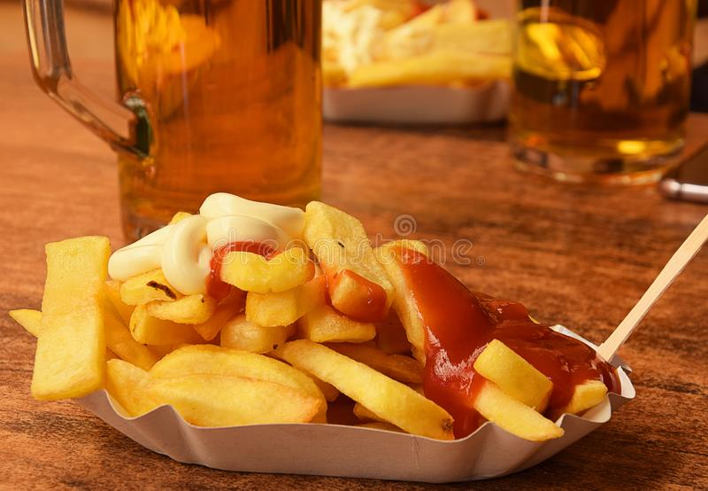 Aria aperta degli alimenti a rapida preparazione - un piatto delle patate fritte con salsa al pomodoro immagine stock