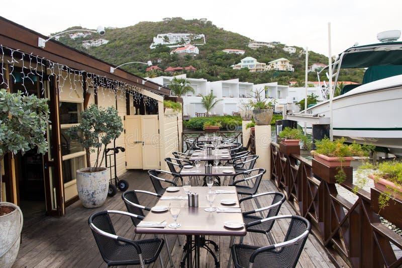 Aria aperta del ristorante nel philipsburg, sint Maarten Terrazzo con le tavole, le sedie e l'yacht in mare Cibo e pranzare all'a fotografie stock libere da diritti