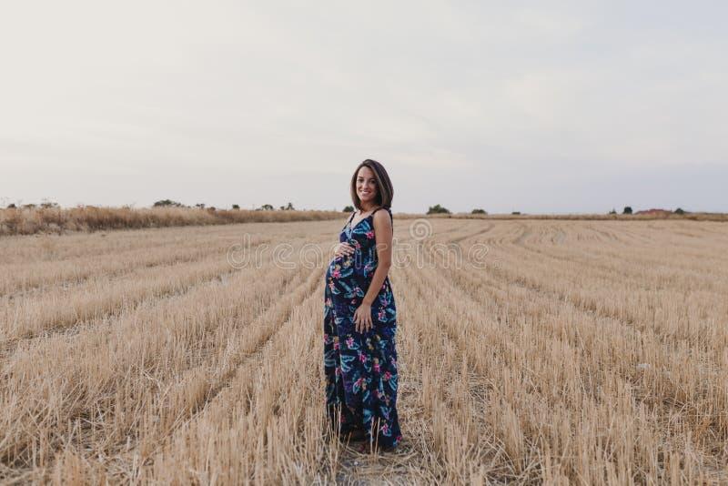 Aria aperta del ritratto di bella giovane donna incinta in un campo giallo Stile di vita della famiglia di aria aperta immagine stock libera da diritti