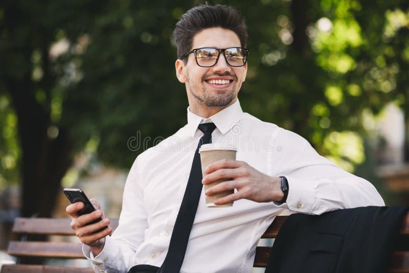 Aria aperta dell'uomo di affari nel parco facendo uso del caffè bevente del telefono cellulare fotografia stock libera da diritti