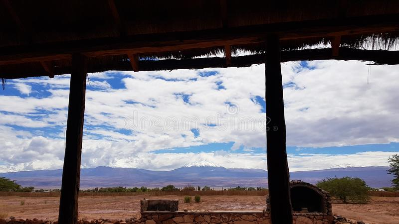 The arid and desolate landscape of the Atacama Desert, Chile. The arid and desolate landscape of the Atacama Desert and the peaks of the snowy volcanoes of the stock photography