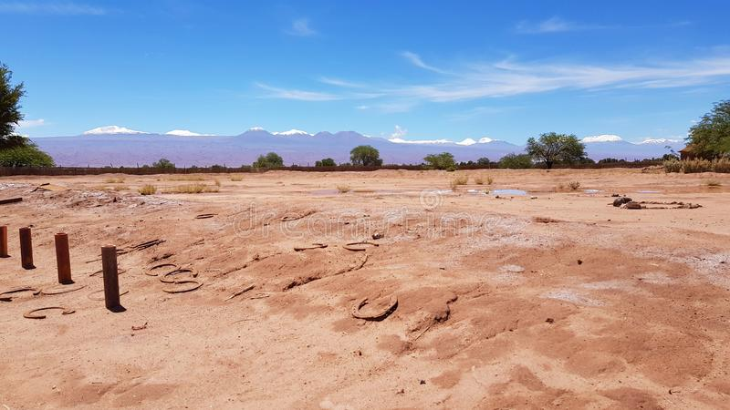 The arid and desolate landscape of the Atacama Desert and the peaks of the snowy volcanoes of the Andes cordillera in the backgrou. Nd royalty free stock photo