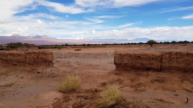 The arid and desolate landscape of the Atacama Desert and the peaks of the snowy volcanoes of the Andes cordillera in the backgrou. Nd stock photo