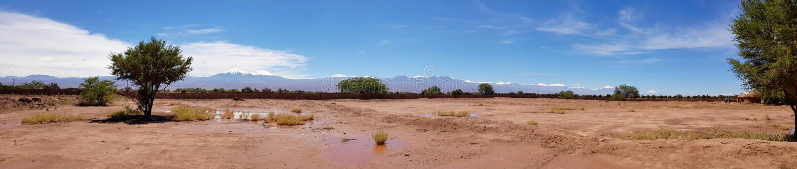 The arid and desolate landscape of the Atacama Desert and the peaks of the snowy volcanoes of the Andes cordillera in the backgrou. View of the arid and desolate stock image