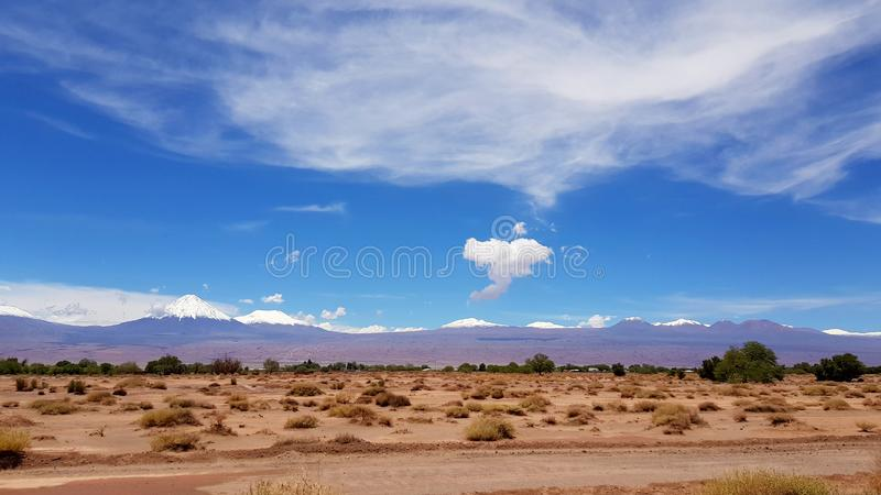 The arid and desolate landscape of the Atacama Desert with the peaks of the snowy volcanoes of the Andes cordillera. The arid and desolate landscape of the royalty free stock image