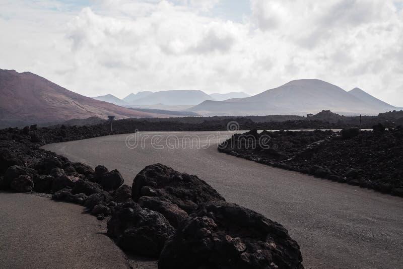 Arid road between volcanoes in Lanzarote. Arid road between volcanoes on the island of Lanzarote stock images