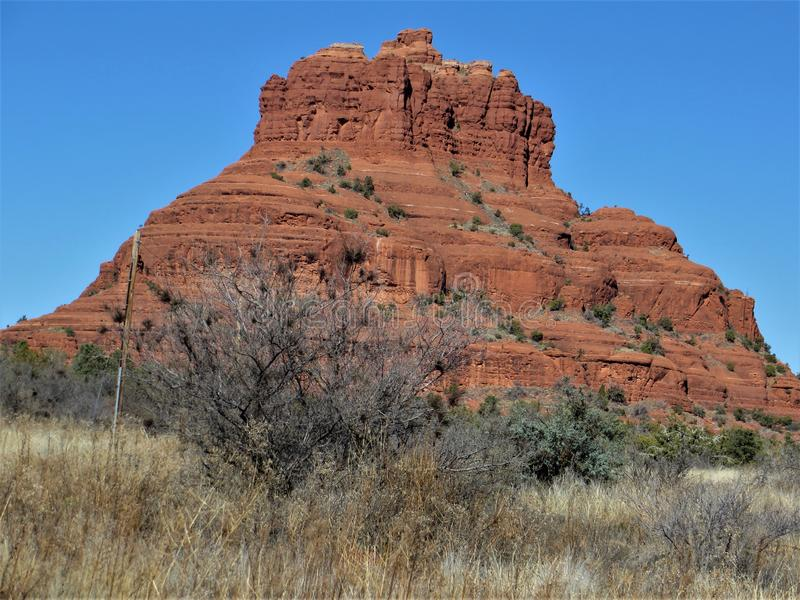 Desert and mountains. Arid Sonoran desert near Sedona, Arizona. Orange-red peak of bare sandstone towers over desert foilage royalty free stock photos