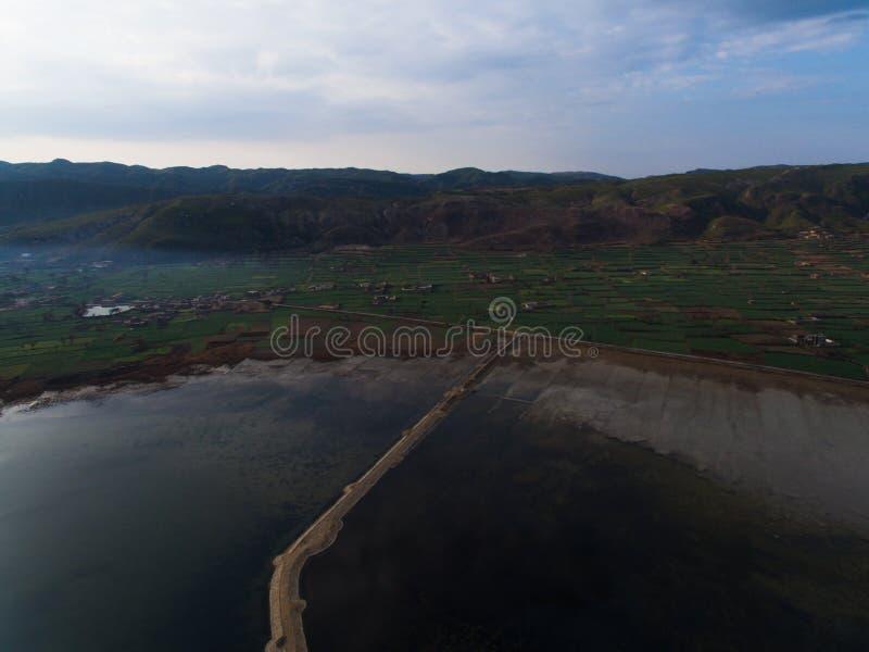 Ariel-Bild von einem See mit Straße und von Feldern entlang seiner Bank lizenzfreies stockfoto