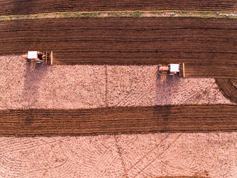 Ariel view of tractor ploughing the farmland. Ariel view tractor ploughing farmland farm farmer drone phantom agriculture machinery plough work eco economy crop royalty free stock photos