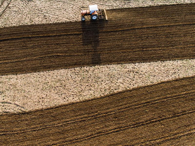 Ariel view of tractor ploughing the farmland. Ariel view tractor ploughing farmland farm farmer drone phantom agriculture machinery plough work eco economy crop stock photography