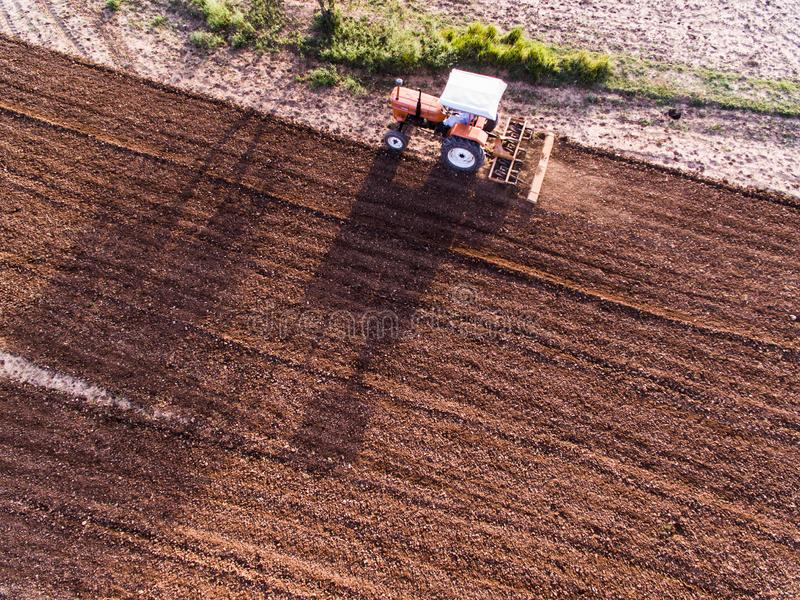 Ariel view of tractor ploughing the farmland. Ariel view tractor ploughing farmland farm farmer drone phantom agriculture machinery plough work eco economy crop stock images