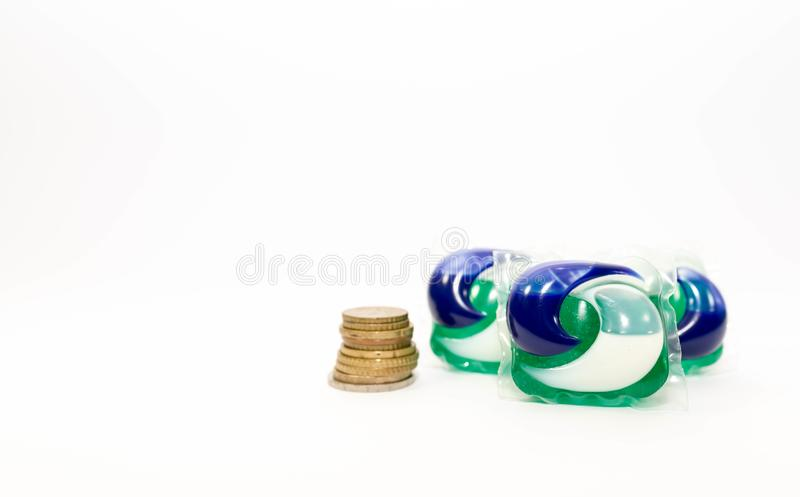 Ariel washing capsules isolated on white background, coin tower , money saving concept. stock photo