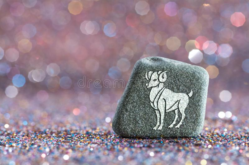 Aries zodiac sign. A green stone with Aries zodiac sign on glitter boke light background stock photo
