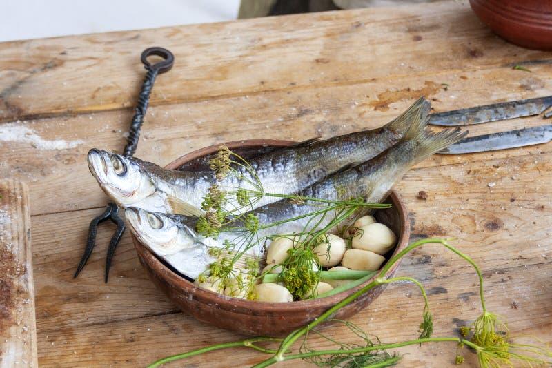 Aringa del pesce in una tazza dell'argilla con le verdure e l'aneto su una tavola agricola di legno immagini stock libere da diritti