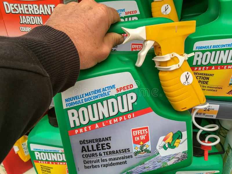 Aris, France - April 27, 2019: Customer buying roundup in a french Hypermarket. Roundup is a brand-name of an herbicide containing. Paris, France - April 27 stock image