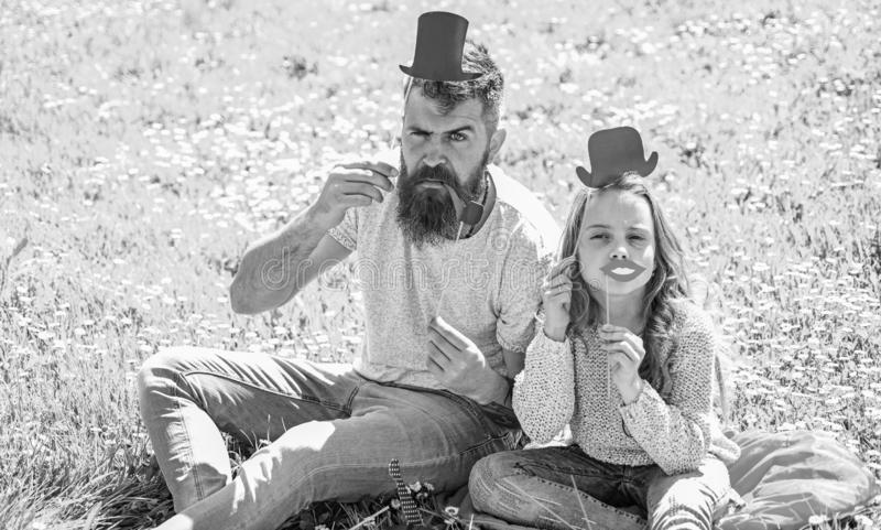 Aristocrates concept. Dad and daughter sits on grass at grassplot, green background. Child and father posing with top. Hat, lips and pipe photo booth attributes stock photo