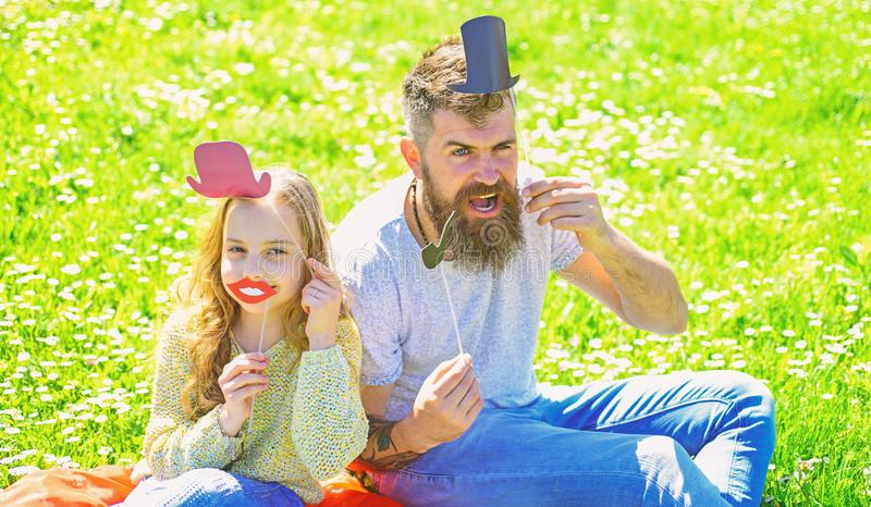 Aristocrates concept. Dad and daughter sits on grass at grassplot, green background. Family spend leisure outdoors. Child and father posing with top hat, lips stock photos