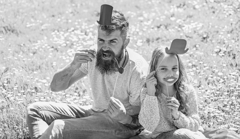 Aristocrates concept. Dad and daughter sits on grass at grassplot, green background. Family spend leisure outdoors. Child and father posing with top hat, lips stock photo