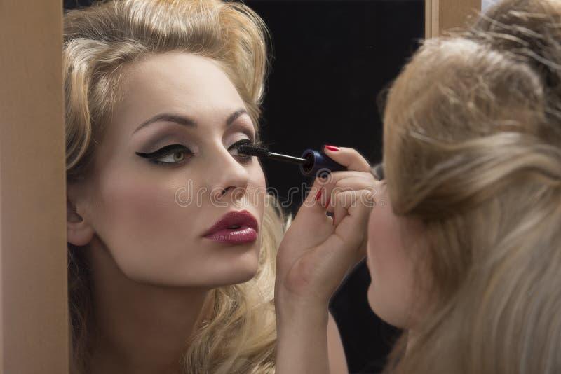 Aristocratic girl applying mascara on mirror royalty free stock image