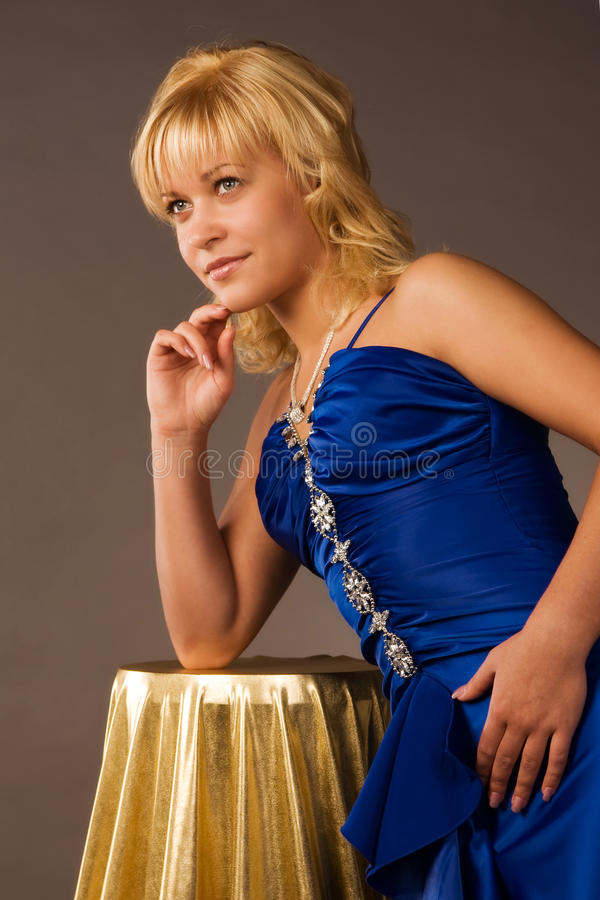 Aristocratic lady in a dark blue dress. In a luxurious boudoir stock image