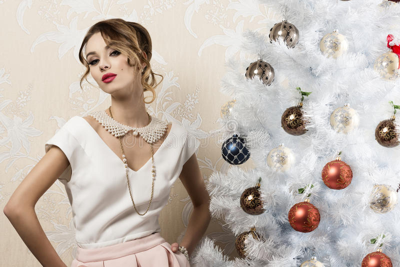 Aristocratic woman near xmas tree. Stunning woman with aristocratic elegant style near christmas decorated tree with hair-style, cute make-up and pearl necklace royalty free stock image