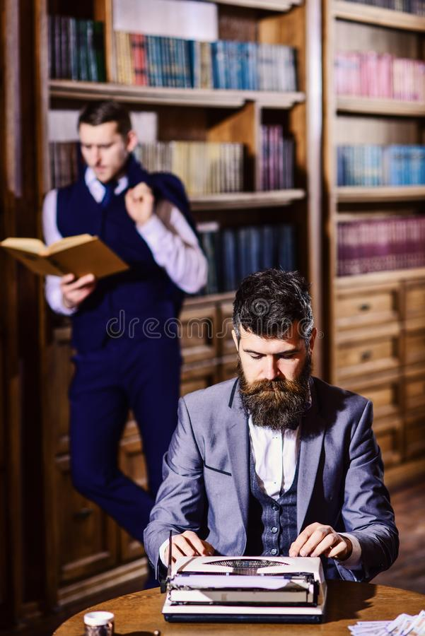 Aristocratie en onderwijsconcept Mens met baard het typen op schrijfmachine stock afbeelding