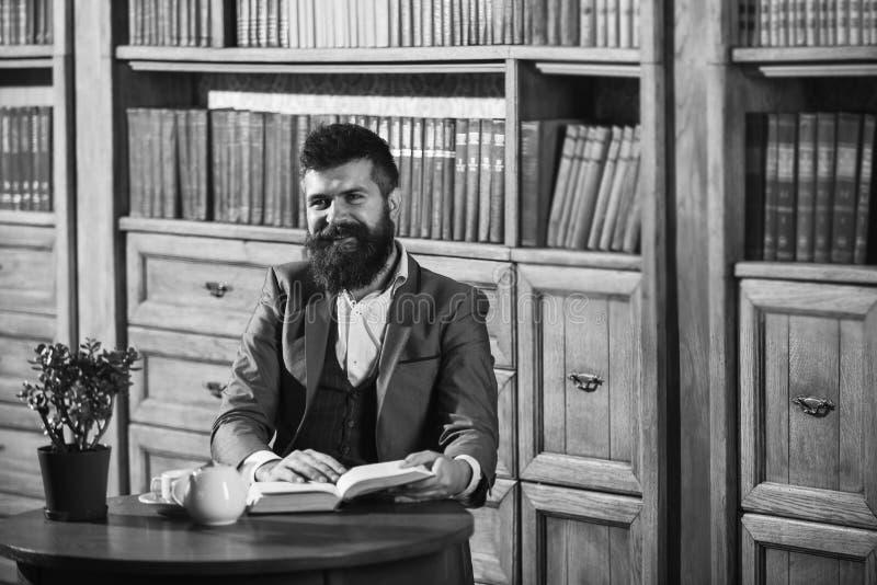 Aristokrat auf lächelndem Gesichtslesebuch Altmodischer Mann nahe Schale, Teekanne Mann in der klassischen Klage sitzt im Weinles stockbilder