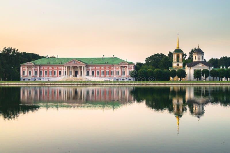 Aristokratisk herrgård och kyrka med klockatornet bredvid dammet i museum-godset Kuskovo, Moskva fotografering för bildbyråer