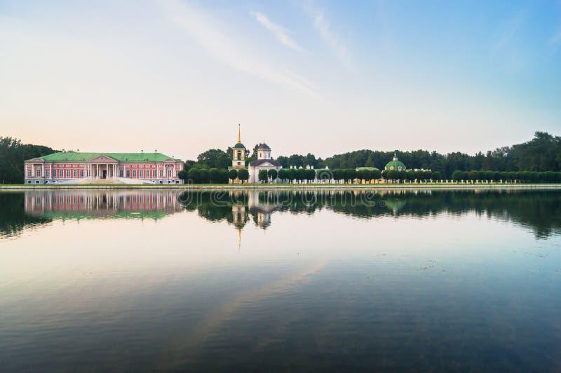 Aristokratisk herrgård och kyrka med klockatornet bredvid dammet i museum-godset Kuskovo, Moskva arkivfoto