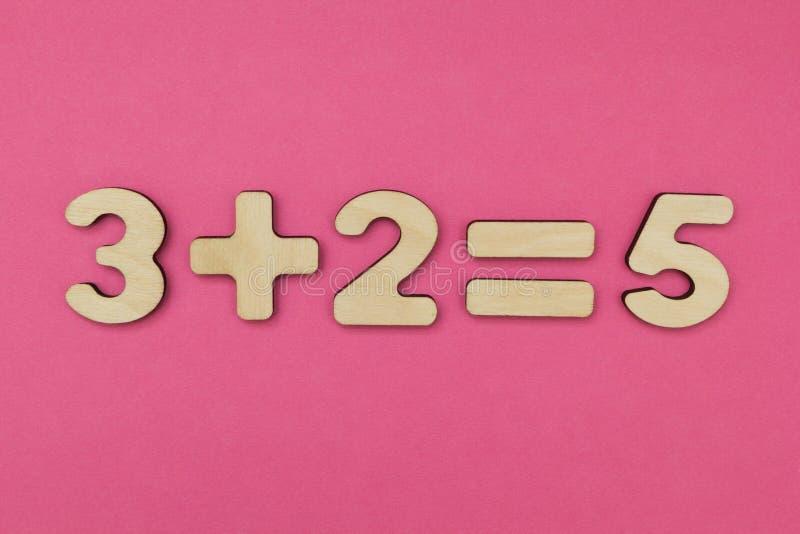 Arithmétique simple pour des enfants Trois plus deux - égal à cinq sur un fond rose lumineux image libre de droits