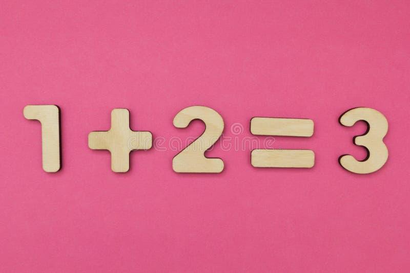 Aritmética simples para crianças Um mais dois - três em um fundo cor-de-rosa brilhante imagem de stock
