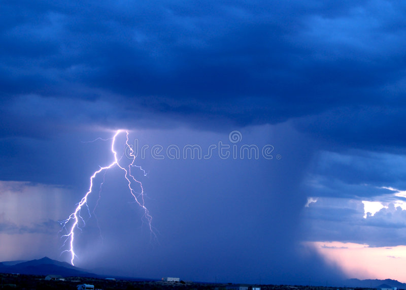 Arizona Monsoon Storm 2006. A late day Arizona Monsoon storm with a lightning bolt striking a nearby mountain royalty free stock images