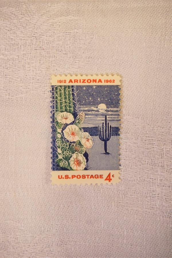 Beetled linen tablecloth supports 4 cent US stamp. `1912 Arizona 1962`postage of the United States is colorfully displayed against white woven linen textile royalty free stock photos