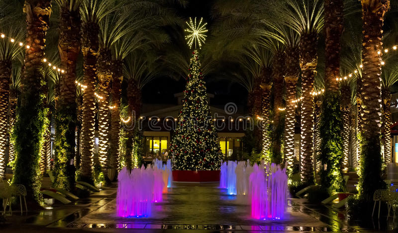 Arizona shopping mall Christmas Tree and lighted palm trees. Lighted palm trees line a pool and colored fountains with a decorated Christmas tree stock image