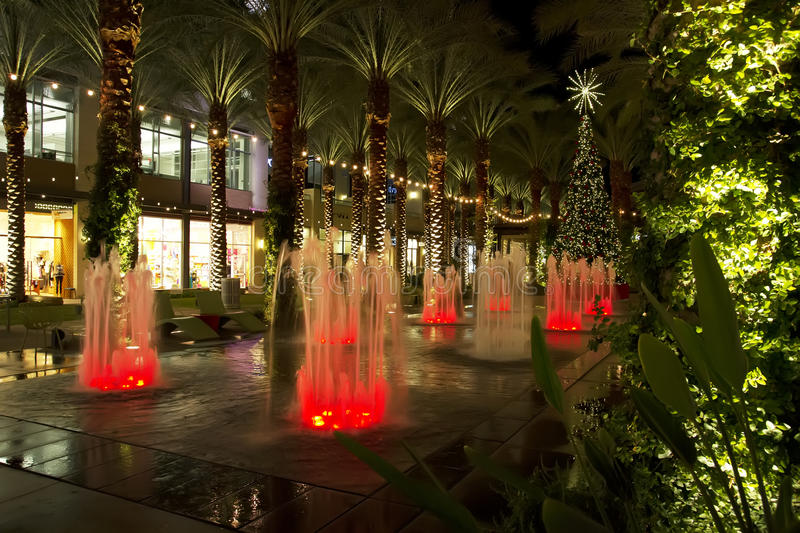Arizona shopping mall Christmas Tree and lighted palm trees. Lighted palm trees line a pool and colored fountains with a decorated Christmas tree royalty free stock images