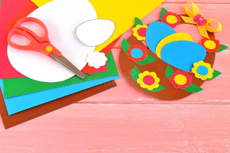 Ark av kulört papper, sax, lim, blyertspennan, påskkorgen och ägg - ställ in för barnkonst arkivfoton