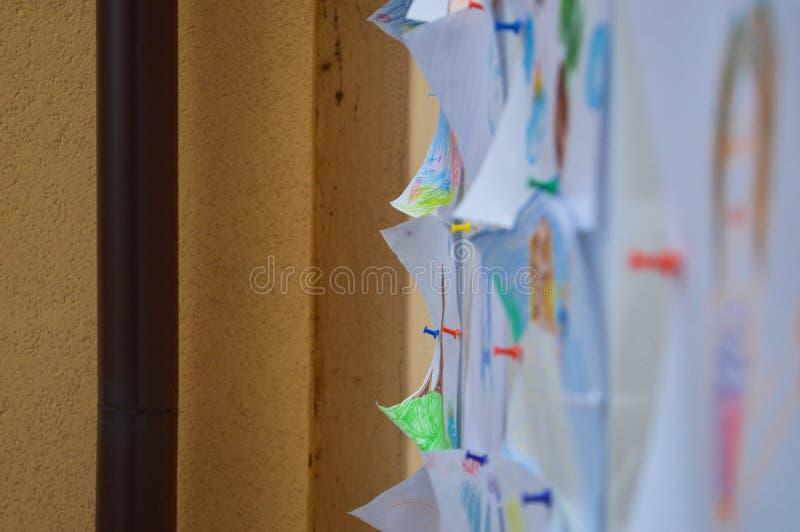 Ark av papper, anmärkningar, teckningar, dokument klämde fast till en svart tavla, en vägg för en påminnelse, undergivenheten av  arkivfoton
