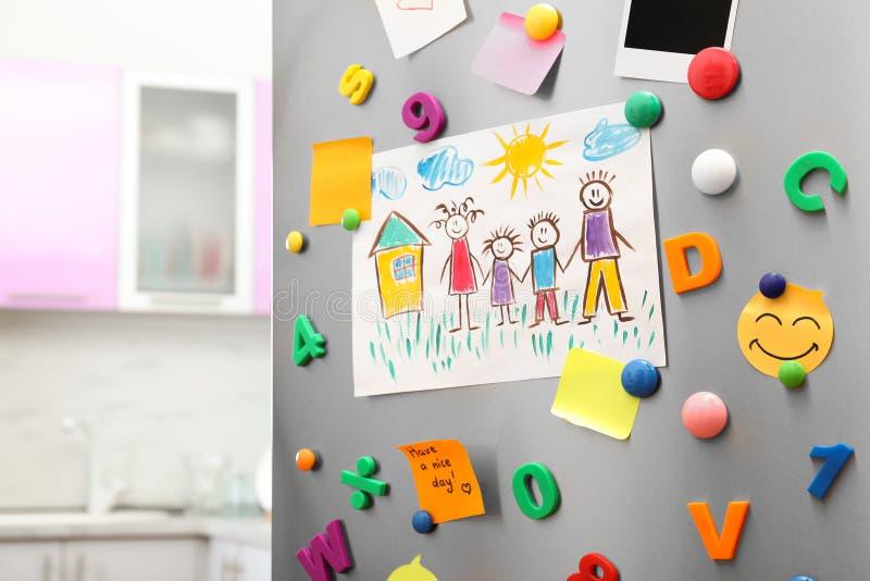 Ark av papper, barns teckning och magneter på kylskåpdörr i kök royaltyfri foto