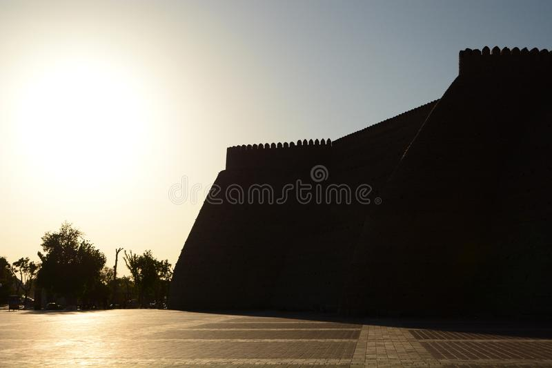Sunset silhouette of The Ark. Bukhara. Uzbekistan. The Ark of Bukhara is a massive fortress located in the city of Bukhara royalty free stock photography