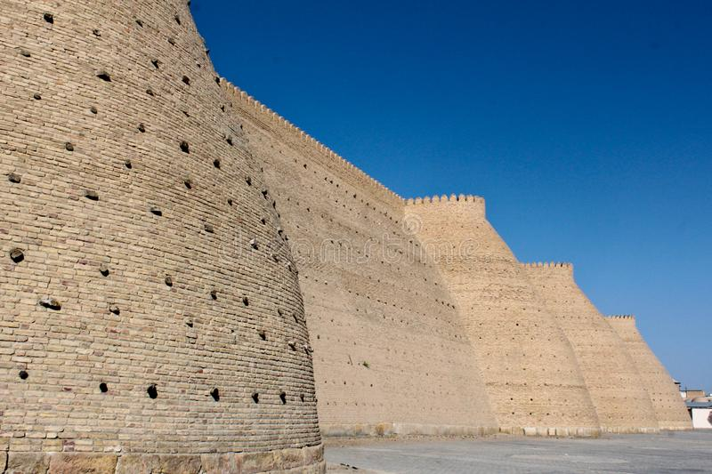 Walls of the Ark in Bukhara. The Ark of Bukhara is a massive fortress located in the city of Bukhara. Currently is a tourist attraction and houses museums stock photos
