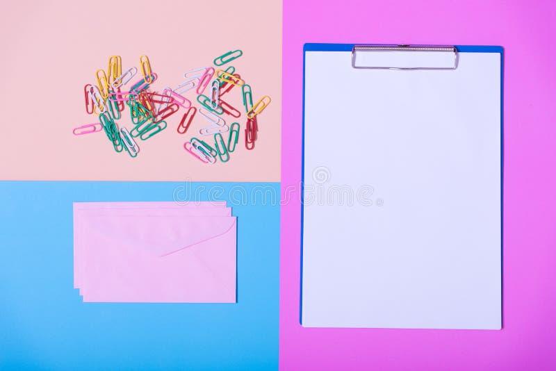 Ark- och kontorstillbehör för tomt papper på färgpapper, minimi arkivbild