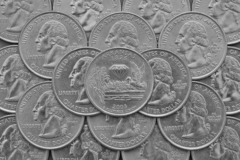 Arkansas State and coins of USA. Pile of the US quarter coins with George Washington and on the top a quarter of Arkansas State royalty free stock photography