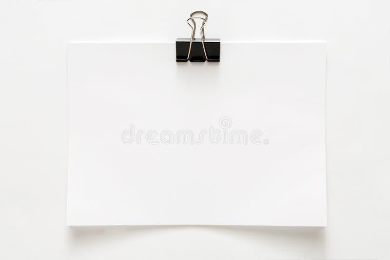 Arket för tomt papper fäste med gemet som isolerades på vit bakgrund arkivbild