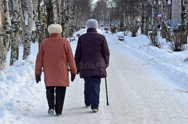 Arkhangelsk, Rússia, fevereiro, 20, 2018 Duas mulheres idosas que andam no parque na rua de Loginov em Arkhangelsk no inverno imagem de stock royalty free