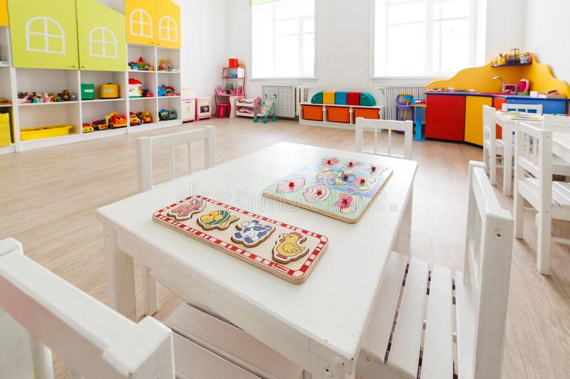 Arkhangelsk, Russia - march 3, 2018: Desk for lessons with toys in bright white game room in the kindergarten. Closeup. royalty free stock photo