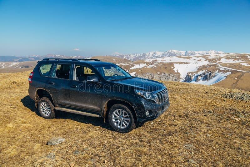 Arkhyz Caucasian berg, Ryssland - APRIL 27, 2017: Svart kryssare Prado för av-väg bilToyota land på Caucasian berg arkivfoto